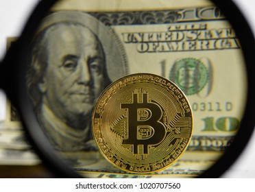 Gold Bitcoin coin and us dollars visible in a magnifying glass