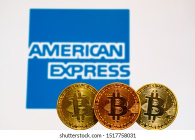 Gold Bitcoin coins with the American Express logo on background screen. A new type of business finance concept. TOKYO, JAPAN - MAY 16, 2019