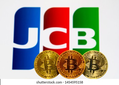 Gold Bitcoin coins with the JCB logo on background screen. A new type of business finance concept. TOKYO, JAPAN - JULY 18, 2019