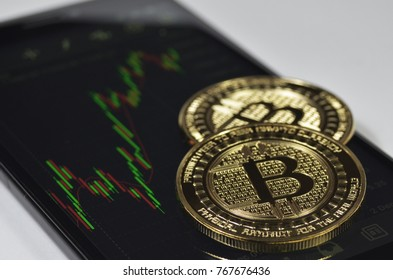 Gold bitcoin coins laying on smartphone market chart bar display