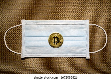 Gold Bitcoin coins with a medical mask