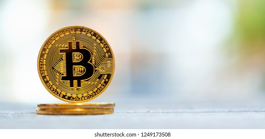 A gold bitcoin cryptocurrency coin on a bright interior room background