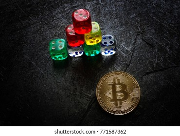 A gold bitcoin and dice in the shape of a pyramid -- risky investment concept