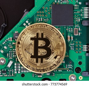 Gold Bitcoin on computer circuit board