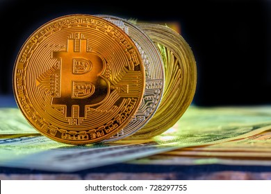 gold bitcoin on a dark background and coiled money.