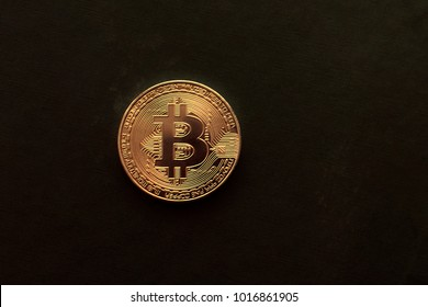 the gold bitcoin on a dark wooden background