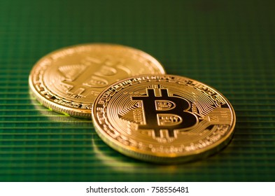 Gold bitcoin on green Motherboard close up.  Bitcoin on the green surface of a solar panel.