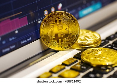 Gold bitcoin on the laptop keyboard on the background of the stock chart