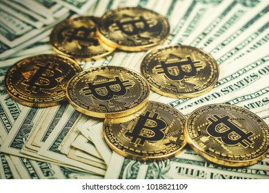 gold bitcoin, on top of dollar stack.