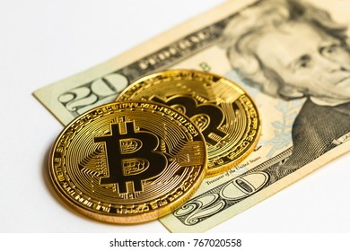 Gold bitcoin on a white background next to us paper money with a face value of dollars