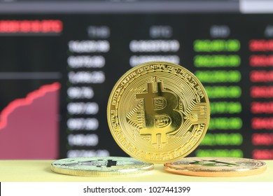 Gold bitcoin placed on wooden floor and digital graph background in concept of cryptocurrency idea for design in your work.