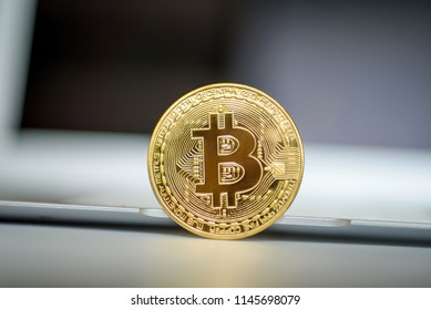 Gold bitcoin, standing on a rib in front of open laptop