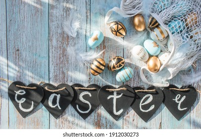 Gold, black, white, blue Easter eggs in a string bag and a sign with the inscription Easter on a blue wooden background. Geometry. The minimal concept of Easter. Top view.