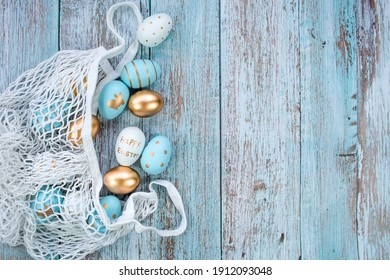 Gold, black, white, blue Easter eggs in a string bag on a blue wooden background. Geometry. The minimal concept of Easter. Top view. An Easter card with a copy of the place for the text.