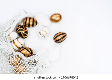 Gold, black, white Easter eggs in a string bag on a white background. Geometry. The minimal concept of Easter. Top view. An Easter card with a copy of the place for the text.