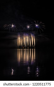 Gold and blue fountain in rich fireworks over surface of Brno's Dam with lake reflection