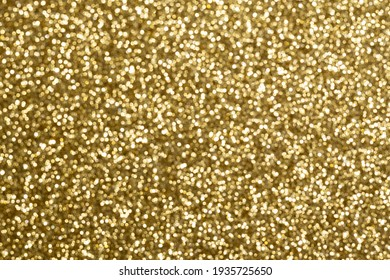 Gold bokeh. The effect of and blurring shiny balls. Defocused holiday lights. Glitter. Abstraction.