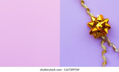 Gold bow on pink, violet background. Festive backdrop for holidays: Birthday, Valentines day, Christmas, New Year. Flat lay style.