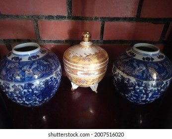 a gold bowl in between two blue chinaware