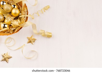 Gold bowl with christmas stars, balls, ribbons on white wood board, top view. Festive xmas background.