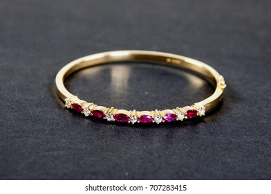 Gold bracelet with ruby and diamonds on a black background.