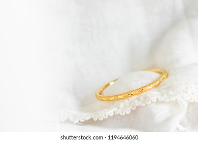 Gold bracelets on delicate fabric made of yarn or thread or lace, gift for romantic moment such as wedding aniversary.