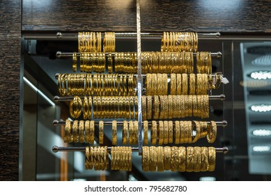 Gold bracelets from yellow gold on a window shop / showcase