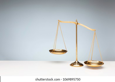 Gold brass balance scale, weight balance, imbalance scale and oval shadow on white desktop with gray background.