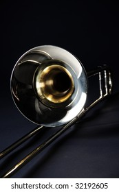 A gold brass trombone isolated against a black background in the vertical format.