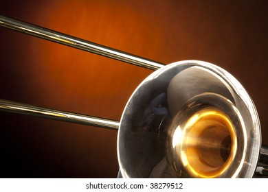 A gold brass trombone wind music instrument isolated against a yellow gold spotlight in the horizontal format.
