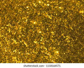 Gold brilliant glitter confetti background for holiday, celebration, happy birthday, web texture and christmas backdrop.