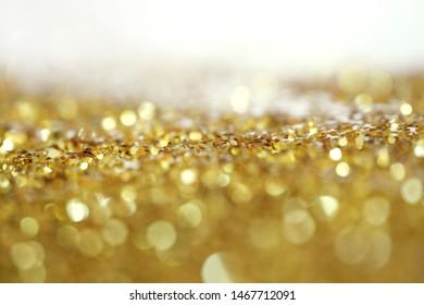 Gold (bronze) glitter shine dots confetti. Abstract light blink sparkle defocus backgound.