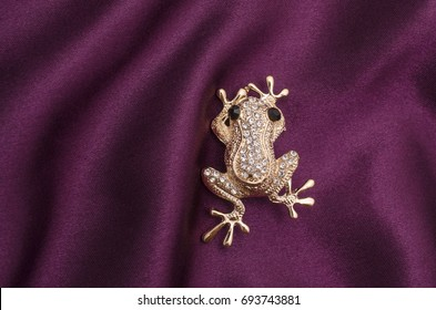 Gold brooch frog with diamonds on silk fabric
