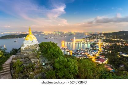 gold buddha stupa, Mondop Roi Phraphutthabat Buddha Footprint, on the mountain and top view of Koh Sri Chang island at night Chonburi Thailand