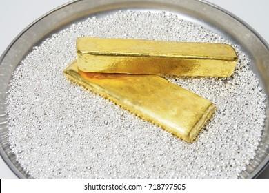 Gold bullion bar on silver grain