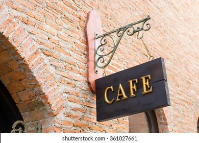 Gold cafe sign above a brick wall