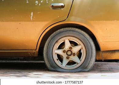 Gold car old, flat tire with rusty alloy wheel