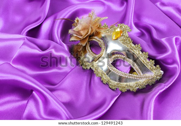 gold carnival mask on purple silk fabric