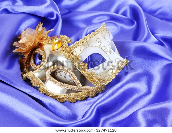 gold carnival masks on blue silk fabric