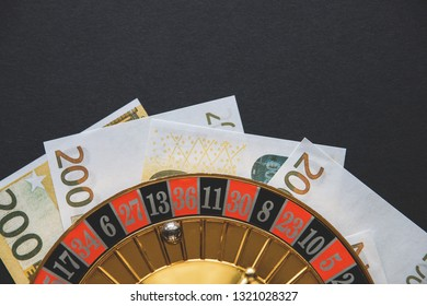 Gold casino theme. Image of casino roulette, poker games, money on the table, all on a dark bokeh background. Place for printing and logo.