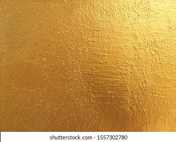 Gold cement wall background for texture abstract