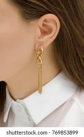 gold chain earrings on female ear