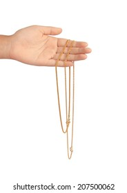 Gold chain in a hand on a white background