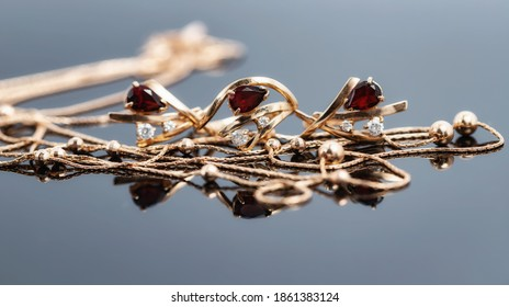 A gold chain necklace with gold beads, a ring and earrings with red rubies lie on a reflective surface