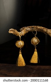 A gold chain with a pearl charm hanging elegantly from a log on a black background.nd.