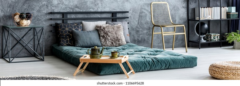 Gold chair placed in dark bedroom interior with raw wall, green mattress bed with pillows and books on metal rack