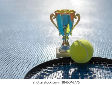 Gold champion trophy, tennis ball and racket on blue background in backlight. First place in tennis tournament. Award for the winner. Sports background, copy space for text