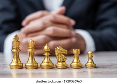 Gold Chess figure team (King, Queen, Bishop, Knight, Rook and Pawn) with businessman manager background. Strategy, Success, management, business planning, tactic, thinking, vision and leader concept