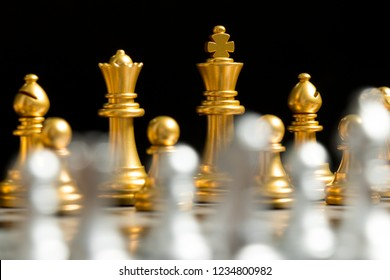 Gold chess team face with silver team on black background (Concept for company strategy, business competition and encounter the problem)