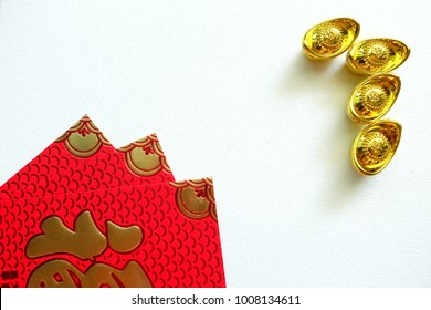 Gold Chinese money and red envelope on white background. Chinese text on envelope meaning good fortune and happiness. Chinese new year festival.
